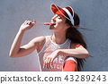 Happy beautiful young woman riding on rollers, eating candy. Summer photo. 43289243