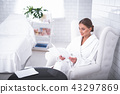 Smiling attractive girl in soft bathrobe sitting in easychair at beauty salon 43297869