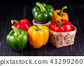 Three sweet peppers on a wooden background 43299260