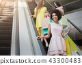 Happy multiracial girls on escalator in mall 43300483