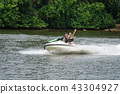 Happy young couple having fun riding on a jet ski 43304927