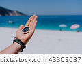 Stretched hand palm with black metal compass against sandy beach and blue sea. Follow your way, goal 43305087