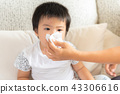 Mother helping daughter blow her nose at home 43306616