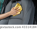 hand with microfiber cloth cleaning leather seat 43314184