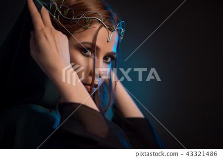 Pretty elf girl tighting green hood on dark background, looking at camera. 43321486