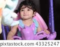 Portrait of a little baby girl on unicorn swing 43325247