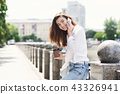Happy girl talking on smartphone while standing outdoors 43326941
