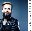 portrait of young bearded hipster guy smiling on gray background 43330090