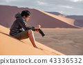 Asian man photographer sitting on sand dune 43336532