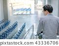 Asian man holding shopping cart on travelator 43336706