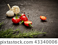 spicy red peppers, garlic and rosemary on a black wooden table 43340006