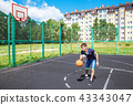 young man playing basketball outdoor 43343047