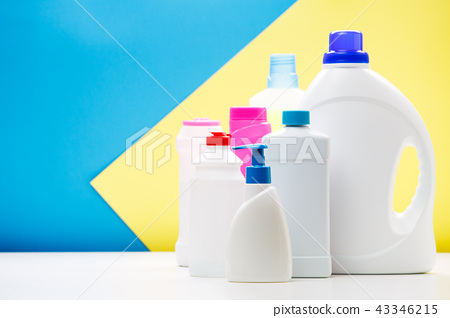 Photo of bottles of cleaning products on white table isolated on blue,yellow background 43346215