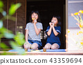 Elementary school girl eating snack at the outskirts of old houses 43359694