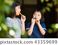 Elementary school girl eating snack at the outskirts of old houses 43359699