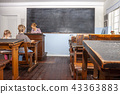 Concept of public primary school education with young boy and girl listening to the female teacher 43363883