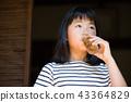 在老房子外緣的小學女孩飲用的大麥茶 43364829