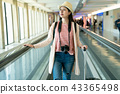 pretty woman standing on the walkway tunnel. 43365498