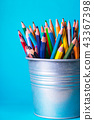 bucket with pencils on a blue background 43367398