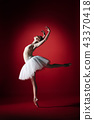 Ballerina. Young graceful female ballet dancer dancing at red studioskill. Beauty of classic ballet. 43370418