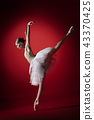Ballerina. Young graceful female ballet dancer dancing at red studioskill. Beauty of classic ballet. 43370425
