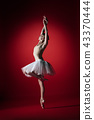 Ballerina. Young graceful female ballet dancer dancing at red studioskill. Beauty of classic ballet. 43370444