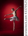 Ballerina. Young graceful female ballet dancer dancing at red studioskill. Beauty of classic ballet. 43370525