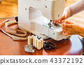 Dressmaker or seamstress works using sewing machine 43372192
