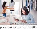 Cheerful seamstress working in personal studio 43376403
