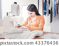 Attentive talented dressmaker sewing new outfit 43376436