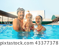 Happy family having fun by the swimming pool 43377378