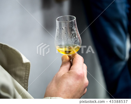 Hand holding a snifter glass filled with whisky 43388537