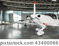 Small private turbo-propeller airplane in hangar 43400066
