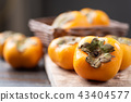 Persimmon fruit in a basket on wooden background 43404577