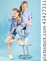 Girls twins in light blue clothes are posing near a bar stool on a blue background. 43427331