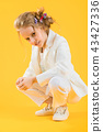 A teenage girl in white clothes is squatting on a yellow background. 43427336