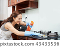 Housewife cleaning stove 43433536