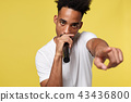 Stylish afro american man singing into microphone isolated on a yellow gold background 43436800