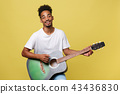 Happy african american musician man posing with a guitar, over golden yellow background. 43436830