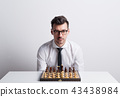 Portrait of a young man in a studio, sitting at the table with chess board game. 43438984