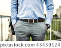 An unrecognizable young businessman with a bag walking on a bridge. 43439124