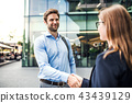 A young businessman and businesswoman shaking hands. 43439129