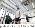 Fit young man with a personal trainer in gym working out, lifting barbell. 43439266
