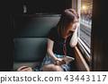 Female passenger listen music, traveling by train. 43443117