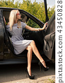 Young attractive girl sits in car opening the door 43450828