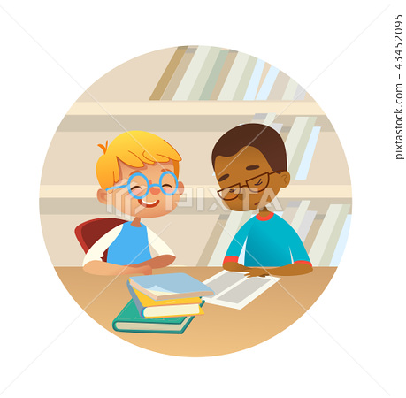 Smiling multiracial boys reading books and talking to each other at school library. School kids 43452095