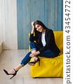Young woman sitting on yellow sofa 43454772
