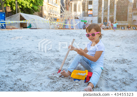 Little girl sitting in the sandbox and playing 43455323