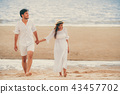Happy young couple walk on the beach on honeymoon. 43457702