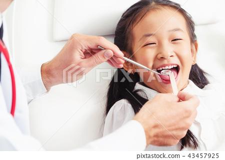 Dentist examining child teeth in dental clinic. 43457925